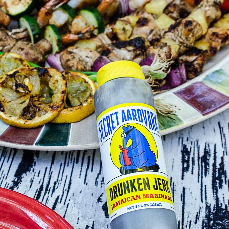 Secret Aardvark Drunken Jerk Jamaican Marinade bottle next to grilled vegetables
