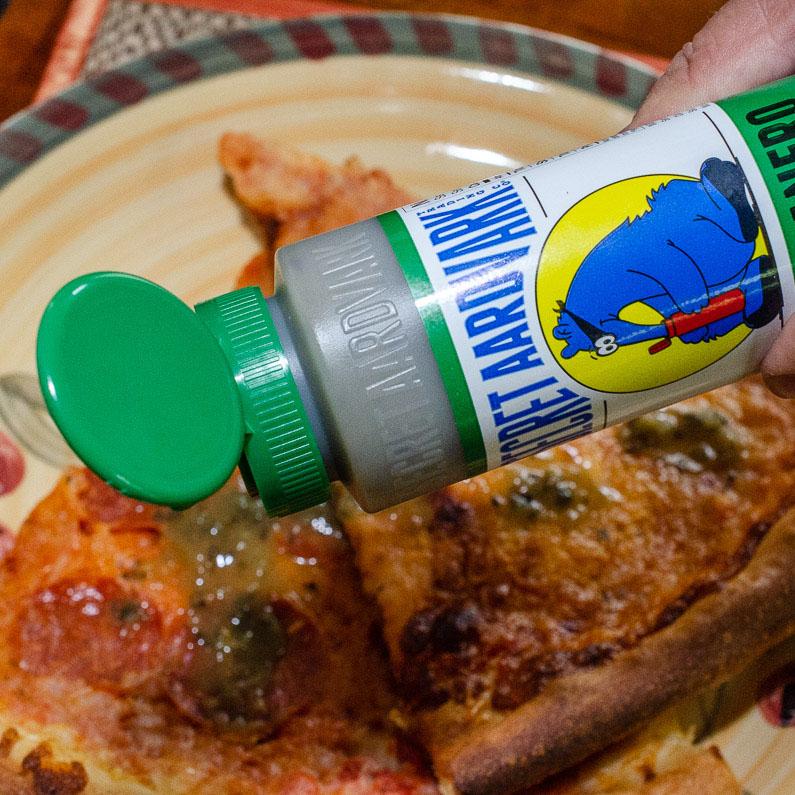 Pouring Secret Aardvark Serrabanero Green Hot Sauce onto pizza