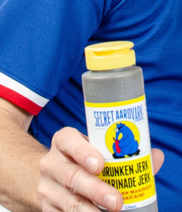 Person in blue shirt holding a bottle of Drunken Jerk marinade