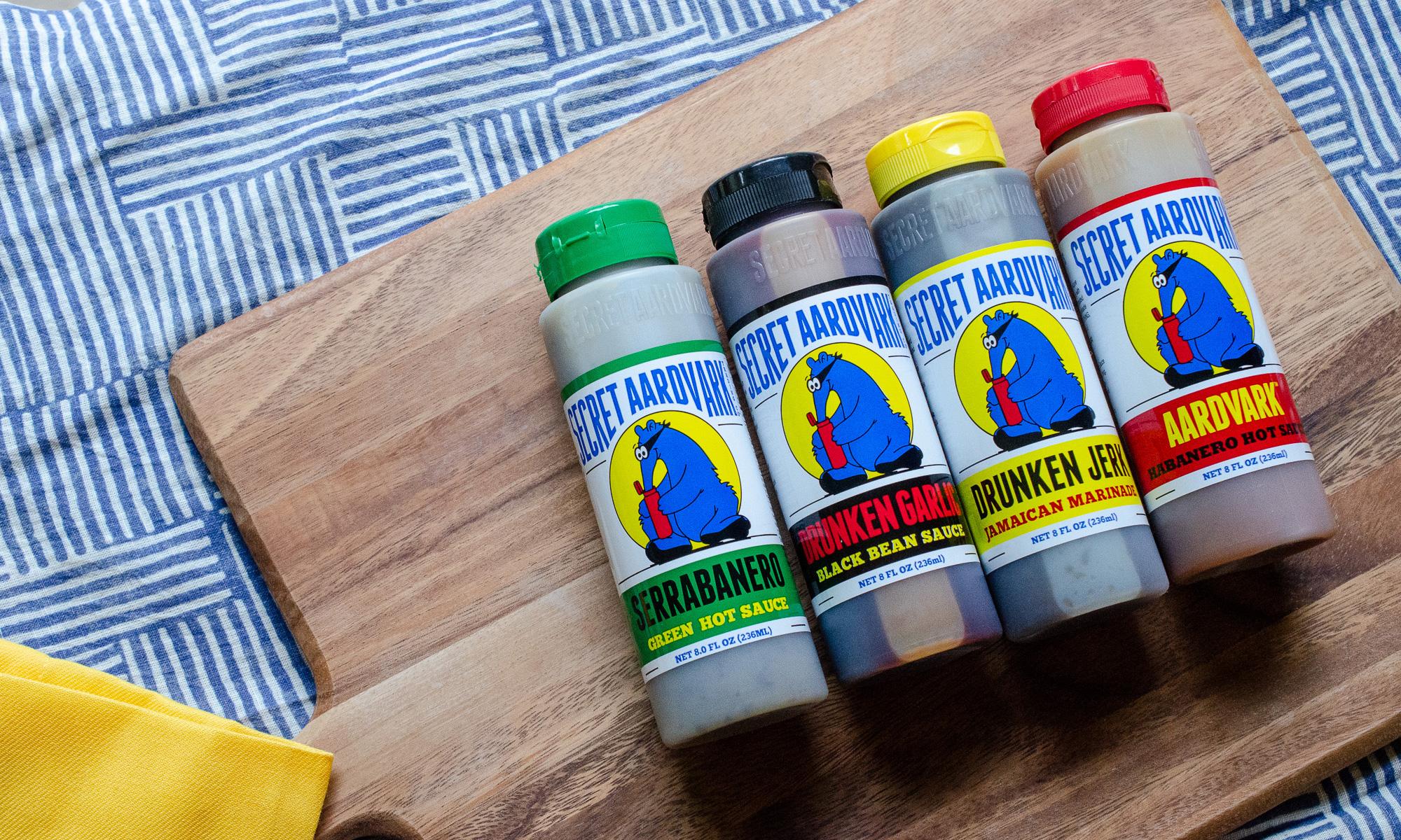 Bottles of Secret Aardvark sauces (Drunken Jerk, Aardvark Habanero, Drunken Garlic, and Serrabanero) on a cutting board