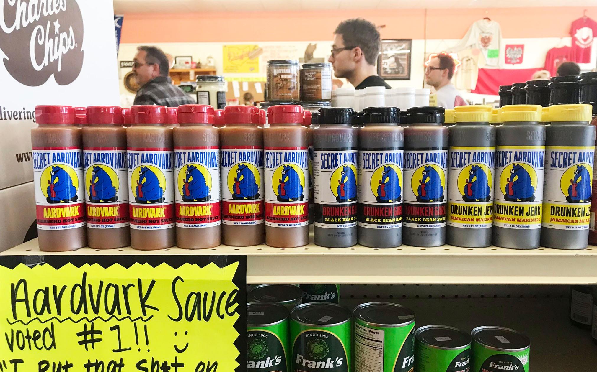 Secret aardvark sauces on a shelf in a shop. Please wait in line in the background